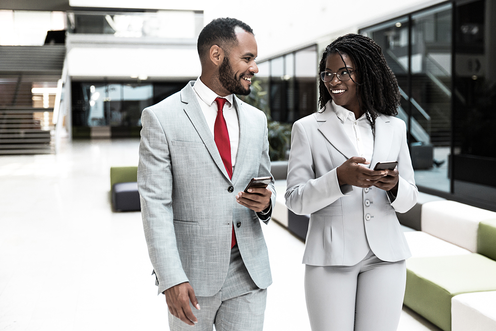 two people smiling at each other while holding their phones